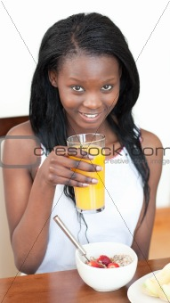 Smiling Afro-American drinking an orange juice