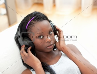 Beautiful woman listening music with headphones lying on a sofa