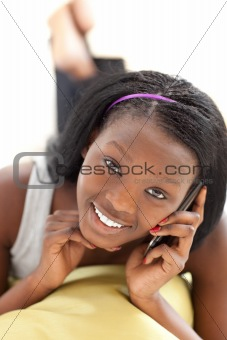 Bright woman on phone lying on a sofa