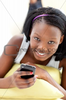 Attractive woman sending a text lying on a sofa