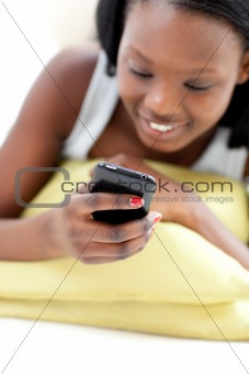 Afro-american woman sending a text lying on a sofa