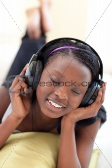 Cute woman listening music with headphones lying on a sofa
