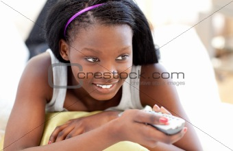 Bright young woman watching TV lying on a sofa