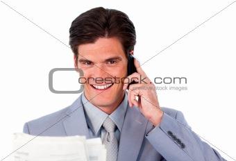 Assertive businessman on phone holding a newspaper