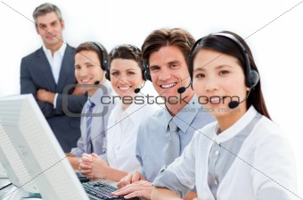 Attractive young woman working in a call center with her colleagues