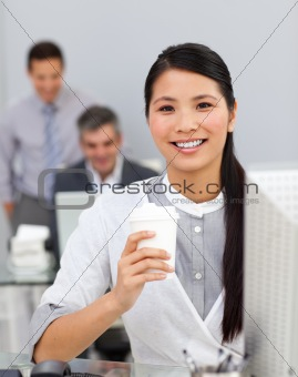 Asian woman drinking coffee in the office