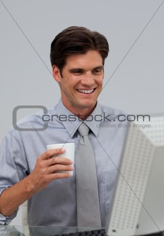 Positive businessman holding a drinking cup