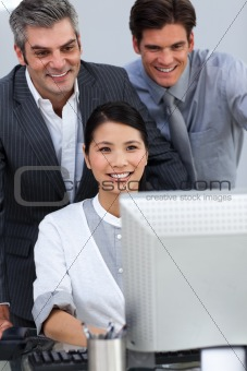 Smiling business partners working together at a computer