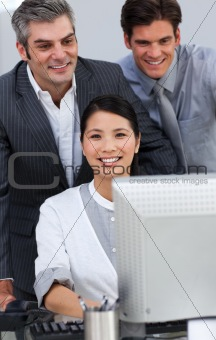 Positive business people working together at a computer