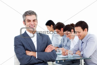Mature manager and his team writting notes in a meeting