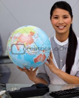 Assertive businesswoman holding terrestrial globe