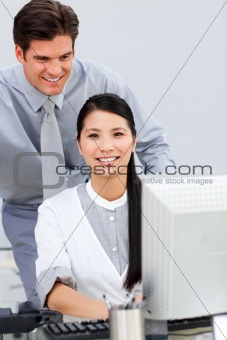 Asian businesswoman and her colleague working at a computer