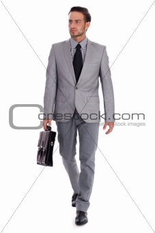 Businessman carrying briefcase and walking