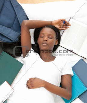 Tired student doing her homework lying on a bed