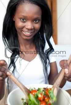 Smiling Afro-american woman preparing a salad