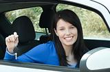 Jolly teen girl sitting in her car holding keys