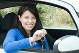 Happy teen girl sitting in her car holding keys