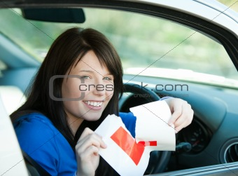 Charming brunette teen girl sitting in her car tearing a L-sign