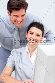 Smiling business woman and her colleage working at a computer