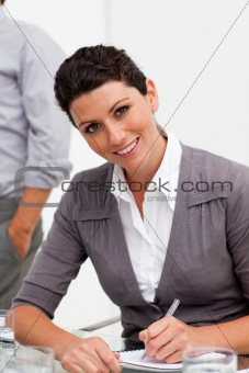 Assertive young businesswoman taking notes