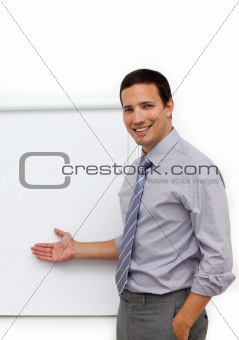 Assertive young businessman pointing at a board