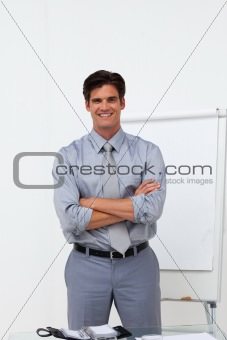 Charming businessman with folded arms in front of a board