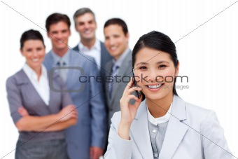 Asian woman talking on phone in front of her team