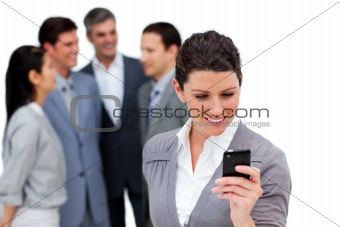 Attractive businesswoman looking at her cellphone in front of he