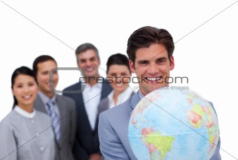 Assertive businessman holding a globe in front of his team