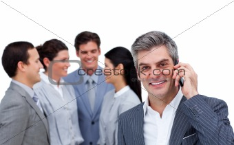 Smiling businessman on phone standing apart from his team