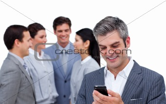 Smiling manager sending a text with a mobile phone with his team