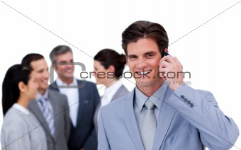 Charismatic businessman on phone standing apart from his team
