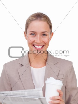 Charismatic businesswoman drinking a coffee reading a newspaper