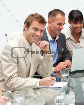 Smiling young businessman making notes