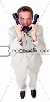 Angry businessman tangle up in phone wires