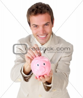 Smiling young businessman saving money in a piggy-bank