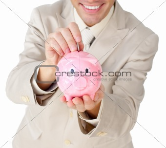 Close-up of a businessman saving money in a piggy-bank