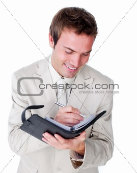 Smiling businessman making notes on his diary