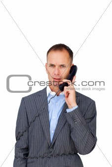 Angry businessman tangled up in phone wires
