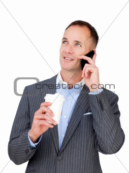 Charming businessman on phone holding a drinking cup