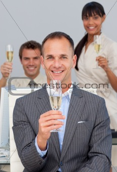 Multi-ethnic business co-workers toasting with Champagne