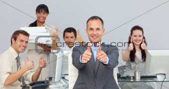 Assertive manager and his team with thumbs up