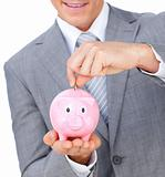 Close-up of a businessman saving money in a piggybank