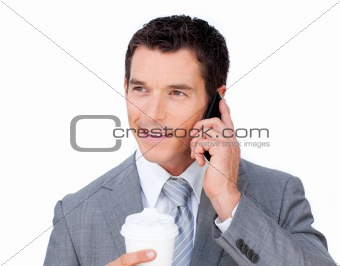 Smiling businessman on phone holding a drinking cup