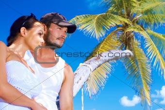 Couple nex to Palm tree