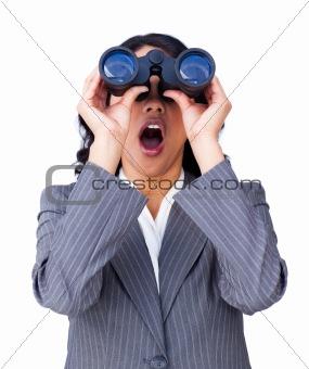 Astonished businesswoman looking through binoculars