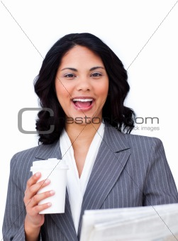 Positive businesswoman drinking a coffee while reading a newspap