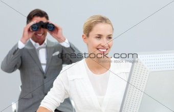 Ambitious manager holding binoculars looking at his colleague's