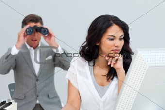 Mature businessman looking his colleague's computer through bino