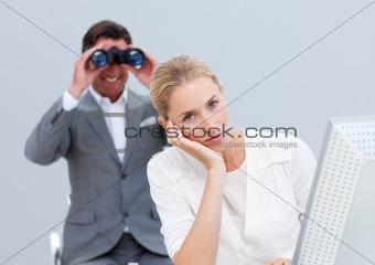 Blond businesswoman annoyed by a man looking through binoculars